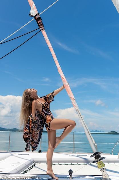 ビーチコートを着た色のついた水着で、髪の長い美しいブロンドの女性。ヨット。豊かな休暇。 Premium写真