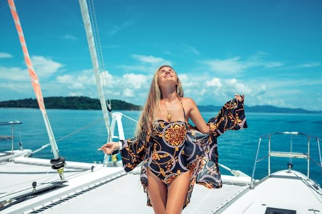 美しく、魅力的な笑顔、長い髪のブロンド、ビーチコートを着た色の水着、立っている間ポーズ、目を閉じてヨットのデッキで。海の喜び。自然。幸福。 Premium写真