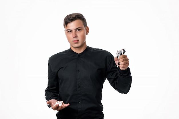 黒いシャツを着た男が、片手に壊れたタバコを持ち、もう片方にタバコのパックを持ってポーズをとります。タバコを放棄するという概念。喫煙は悪です Premium写真