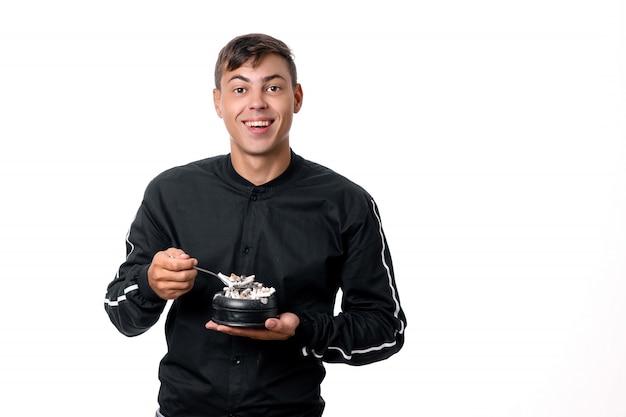 Никотин это яд. вредные привычки: молодой человек ест сигареты ложкой из пепельницы. курение убивает. Premium Фотографии