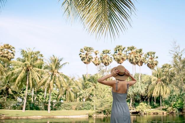 ドレスを着て麦わら帽子の幸せなツーリストの女性は彼女の腕を横に広げた Premium写真