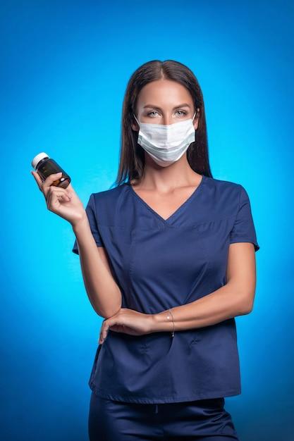 Красивая брюнетка с ее волосы позирует стоя на синем фоне в защитной маске впереди, держа в руке банку лекарств. медсестра. здравоохранение. вертикальное фото. Premium Фотографии