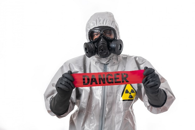 灰色の防護服を着た男が頭にフードを被り、防毒マスクを着用し、白い背景の上に立って、赤いハザードテープを手に持ってポーズをとる。危険テープ。保護。 Premium写真