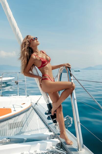 セクシーな赤いビキニと赤いサングラスを着てヨットの上で美しい金髪の女性 Premium写真