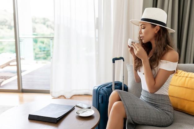 ホテルの部屋に座って荷物を持って帽子をかぶって帽子の若い旅行者女性、旅行荷物を持ってビジネス旅行旅行到着後にリラックスを待っている美しい女性 Premium写真