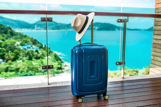 Синий дорожный чемодан со шляпой стоит на открытом балконе с видом на море и красивую природу. отпуск и путешествия Premium Фотографии
