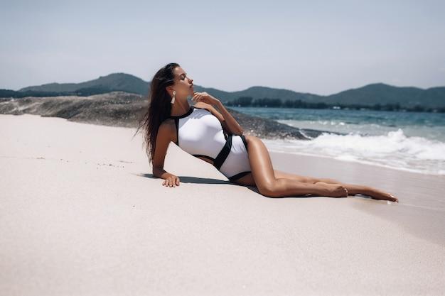 Симпатичная модель девушки в модном купальнике лежит и загорает на пустынном пляже возле скал. Premium Фотографии
