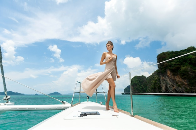 ヨットの端に立っている白いベージュのドレスでかわいい若い女性の屋外撮影 Premium写真
