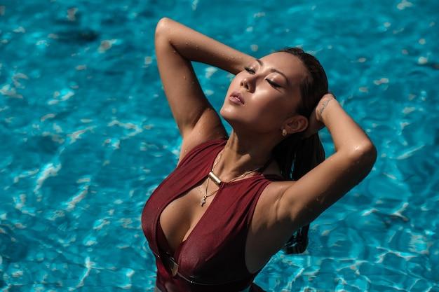 Азиатская сексуальная женщина в бургундском бикини у бассейна в солнечный день, яркие тона, модная поза бикини Premium Фотографии