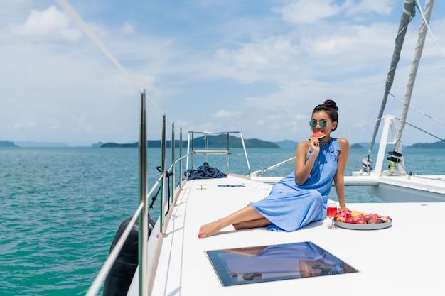 ヨットの上の青いドレスの美しいアジアの女性はシャンパンを飲み、果物を食べる Premium写真