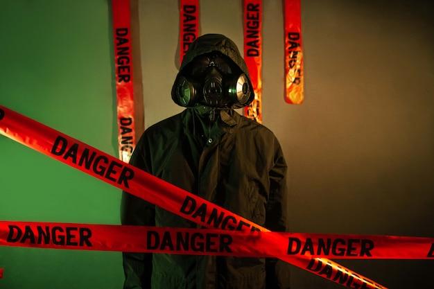 顔に防毒マスク、頭にフード付きの暗い防護服を着た男。危険の概念 Premium写真