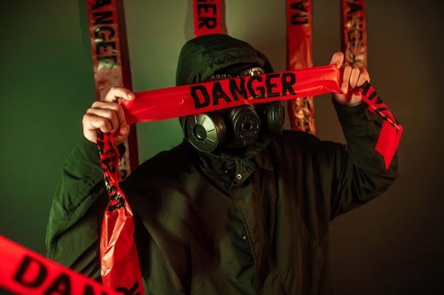 Мужчина в темном защитном костюме с противогазом на лице и капюшоном на голове позирует возле зеленой стены, держа на лице ленты опасности. концепция опасности Premium Фотографии