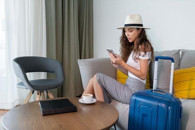 ソファの上の電話に座ってポーズスカートと白いトップの帽子のかわいいブルネット Premium写真