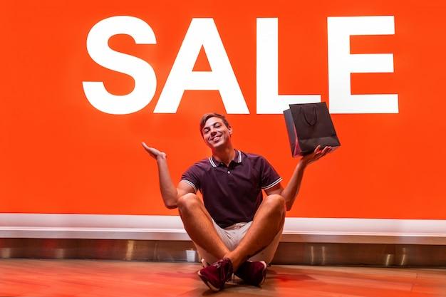 言葉販売で大きなオレンジ色の看板の近くに座ってポーズをとって、彼の手で購入するとパッケージを上げる若い男の笑みを浮かべてください。喜びの感情。ビッグセール。割引。ブラックフライデー。 Premium写真