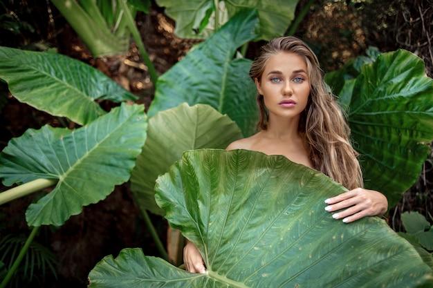 大きな緑の葉を持つ美しい白人スタイリッシュな若い女性の肖像画 Premium写真