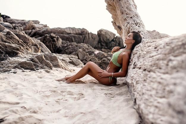 古い木の近くのビーチでポーズの水着で美しい少女セクシーなブルネット Premium写真