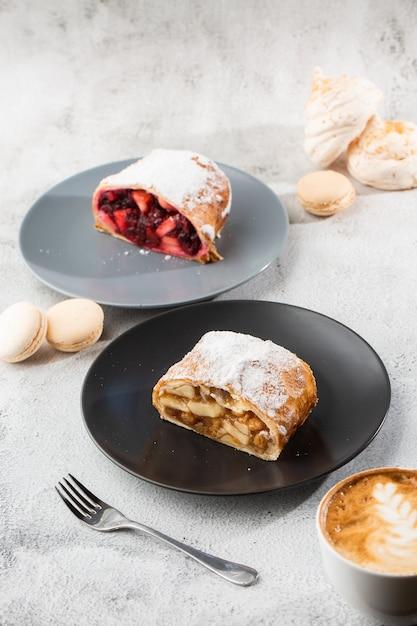 Домашний традиционный австрийский яблочный штрудель со свежими яблоками, орехами и сахарной пудрой. меню для кафе. кусок пирога на черной плите, белой чашке на белой мраморной предпосылке. вертикальное фото. Premium Фотографии