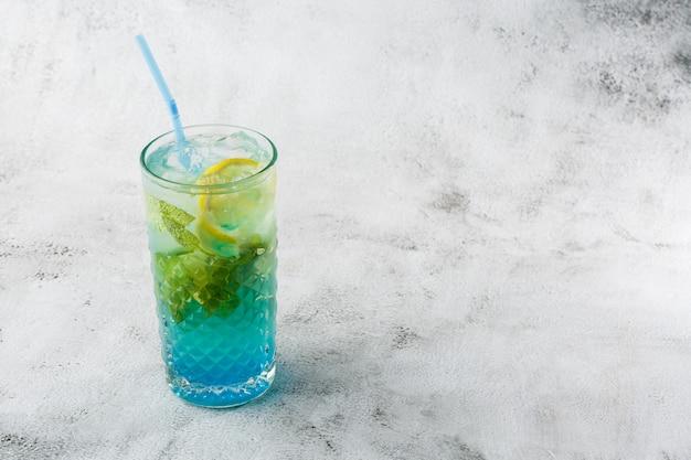 Голубой коктейль с кубиками льда и ломтиками лимона и лайма. голубая лагуна летний коктейль. замороженный голубой лимонад. вид сверху, копирование пространства. реклама для кафе. барное меню. горизонтальное фото. Premium Фотографии