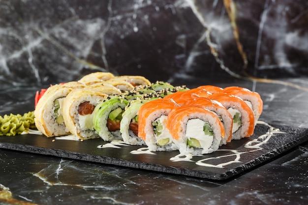 Различные виды суши подают на черном мраморном фоне. суши-меню для японской кухни. японский набор суши. роллы с тунцом, лососем, креветками, крабом, икрой и авокадо. горизонтальное фото. Premium Фотографии