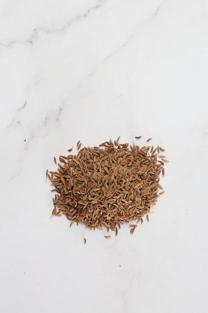 白で隔離される上からキャプチャされたクミンの種子の山。子午線フェンネルおよびペルシャクミンとしても知られるキャラウェイの種子。芳香族駆虫剤。健康と食のコンセプト Premium写真