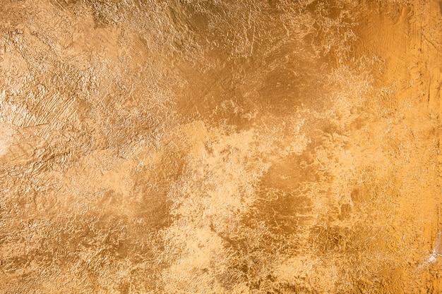 抽象的なゴールドのテクスチャ。黄金の石膏で着色された壁。 Premium写真