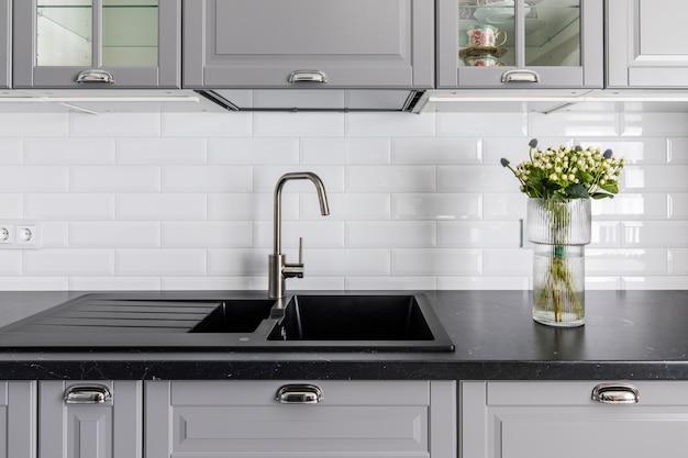 Интерьер современной кухни. темная столешница и раковина, серые фасады шкафчиков. ваза с цветами украшает стол Premium Фотографии