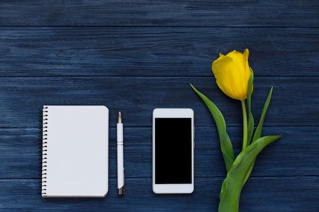 春の黄色いチューリップ、空白のノートブック、ペン、白いスマートフォン。フラット横たわっていた、トップビュー。 Premium写真