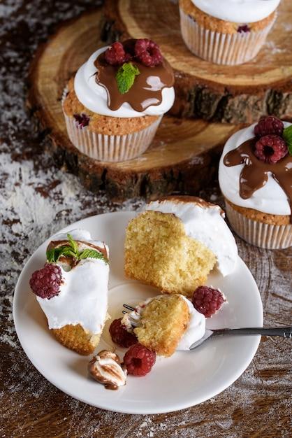 ホワイトクリームのカップケーキにチョコレートを注ぎ、ラズベリーとミントを混ぜます。 Premium写真
