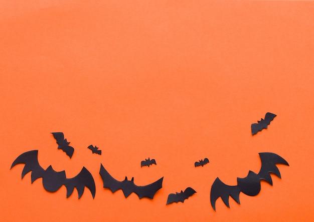 オレンジ色の背景にハロウィーンコウモリ Premium写真