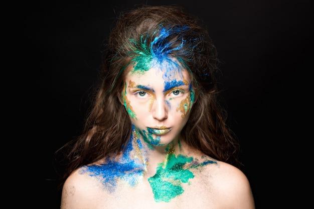 Красивое лицо с цветной краской на черном Premium Фотографии