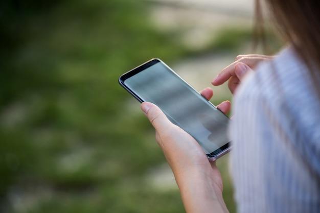テキストメッセージまたはプロモーションコンテンツの空白の画面を持つ携帯電話を保持している女性の手のクローズアップ Premium写真