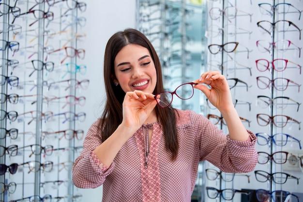 Счастливая женщина, выбирая очки в магазине оптики Premium Фотографии