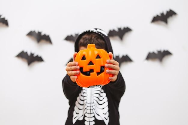 Милый парень в хеллоуин костюм позирует с тыквой. Premium Фотографии