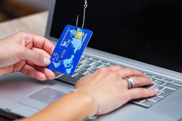 Фишинг кредитной карты. фишинговая афера с помощью кредитной карты в рыболовном крючке. Premium Фотографии