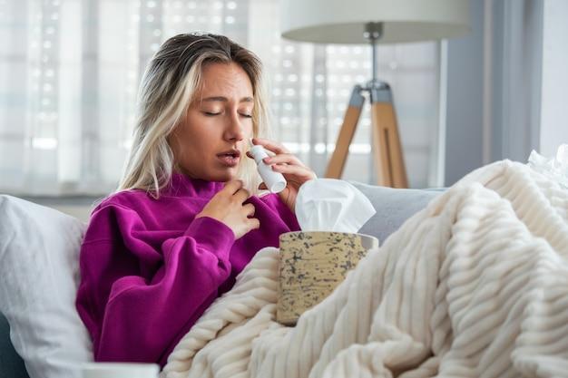 女性が風邪をひき、インフルエンザが組織にくしゃみをしました。 Premium写真