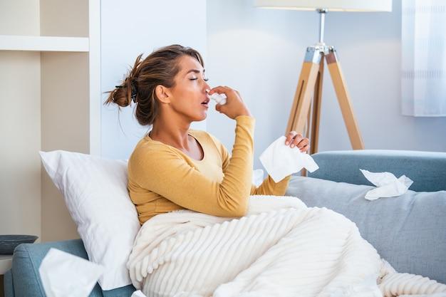 Женщина простудилась и грипп чихает в ткани. Premium Фотографии