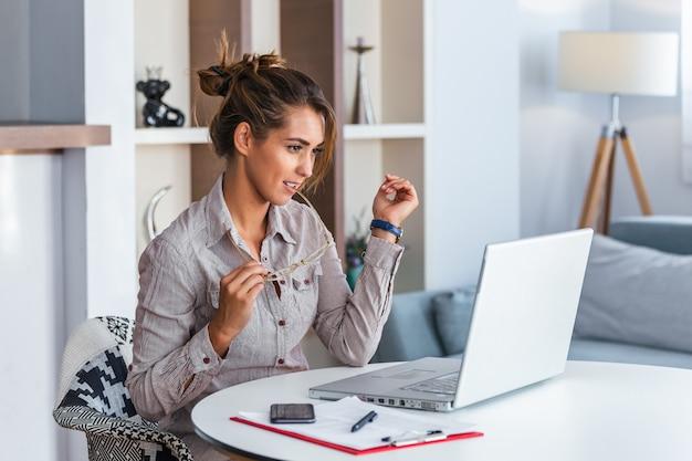 Женщина работая с выражением компьтер-книжки дома разочарованным. Premium Фотографии