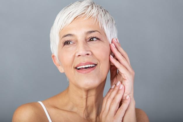 顔に手を浮かべて成熟した女性の美しさの肖像画。アンチエイジング治療後新鮮な感じ幸せな年配の女性のクローズアップ顔。完璧な肌でカメラを見て笑顔の美しさ。 Premium写真