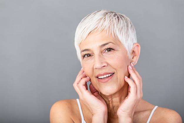 彼女の完璧な肌に触れるとカメラ目線の美しい年配の女性の肖像画。灰色の背景に分離された顔をマッサージしわと成熟した女性の顔をクローズアップ。老化プロセスの概念。 Premium写真