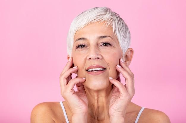 彼女の完璧な肌に触れるとカメラ目線の美しい年配の女性の肖像画。ピンクの背景に分離された顔をマッサージしわと成熟した女性の顔をクローズアップ。老化プロセスの概念。 Premium写真