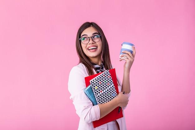 本とコーヒーの手で行く女子学生または女性教師の肖像画を笑っています。教育、高校、人々のコンセプト-メガネで幸せな笑顔若い女教師 Premium写真