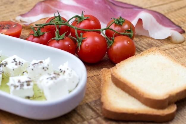 チェリートマト、チーズ、プロシュート、木製のテーブルに乾杯 無料写真