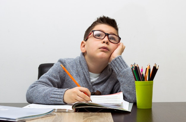 Мальчик расстроен над домашним заданием, пишет дома. мальчик учится за столом. малыш рисует карандашом. Бесплатные Фотографии