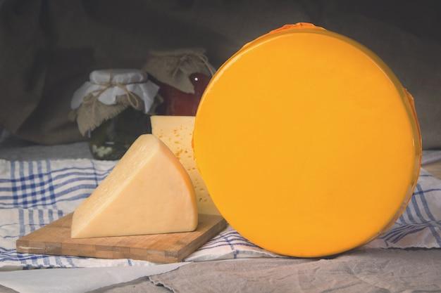 Сыр на деревянной доске, большая сырная голова. Premium Фотографии
