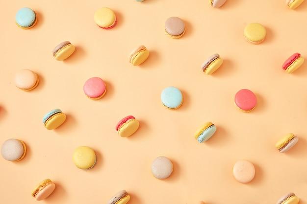 黄色の桃の背景にカラフルなフレンチクッキーマカロンのパターン Premium写真