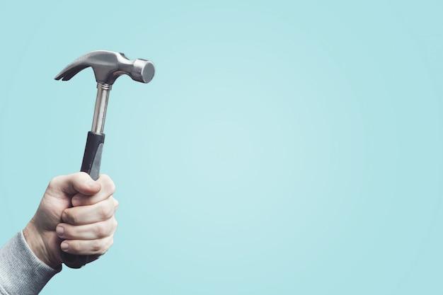 Человек, держащий старинный молоток, инструмент в руке. Premium Фотографии