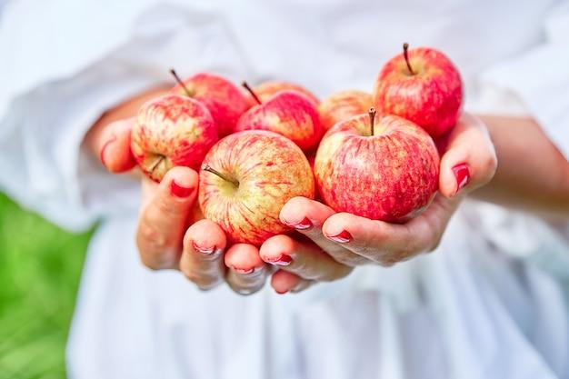 手に新鮮で自然、ジューシーなリンゴ。手は緑の草を背景にリンゴを保持します。 Premium写真