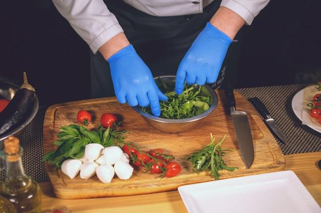 調理された手袋でシェフの手。シェフは、バジル、チェリートマト、ルッコラとモッツァレラチーズのグルメ料理を作っています。 Premium写真