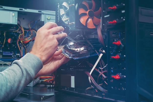 コンピューターを修理する技術者、マザーボード上のコンポーネントを交換するプロセス。 Premium写真