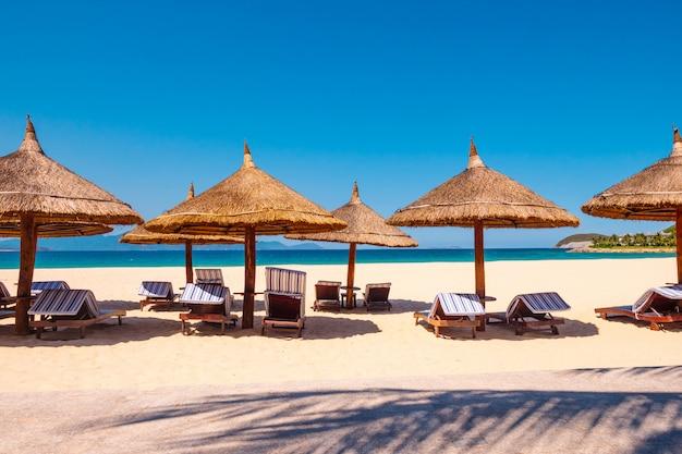 Роскошный курорт. зонтик с шезлонгами на пляже возле океана. Premium Фотографии